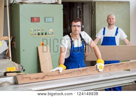 Two Worker In Workshop Using Saw Machine