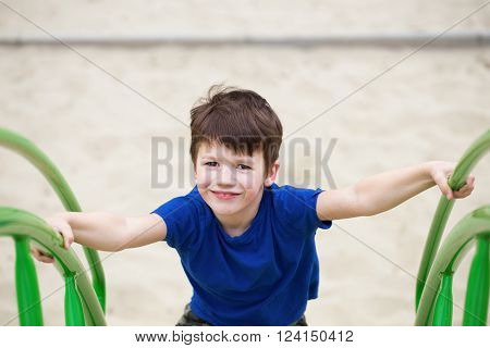 Boy climbing on jungle gym in park outdoor