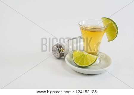 Glass of tequila with lime on the white background. Tequila shot. Gold Mexican tequila. Tequila