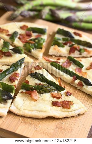 Green asparagus and bacon tarte flambee or Flammkuchen a typical Alsatian and South German dish photographed on wooden board with natural light (Selective Focus Focus one third into the image)