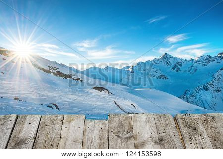 View from wooden table to sunset in winter mountains covered by snow. Concept with shining sun on the blue sky