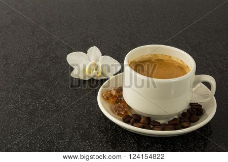 Coffee cup and white orchid on the black background. Cup of coffee. Coffee break. Morning coffee. Coffee cup