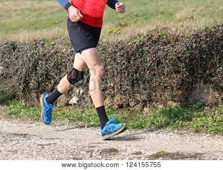 Runner During The Cross-country Race With Knee Wrapped By A Knee Brace