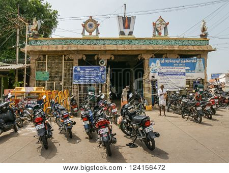 Trichy, India - October 15, 2013: Entrance to Anna Mandapam with Lord Vishnu symbols and avatars on top and a bunch of motorcycles in front. Symbols are Chakra, Conch, Flame, and Garuda avatar on both corners.