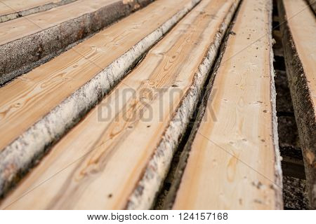 At sawmill. Image of wooden boards lying in row, close-up