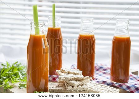 Natural and fresh carrot juice in small bottles with fresh celery and plain rye cakes galette rye on light background