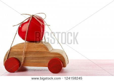 Wooden car with a red heart  tied to it on a pink wooden table over white background