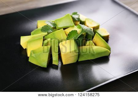 Fresh diced avocado on black plate, close up