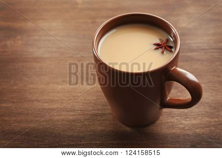 Milk tea with anise on wooden background.