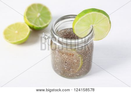 Chia seeds beverage with lime in glass jar on white background