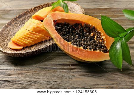 Halved papaya with slices on a wooden plate