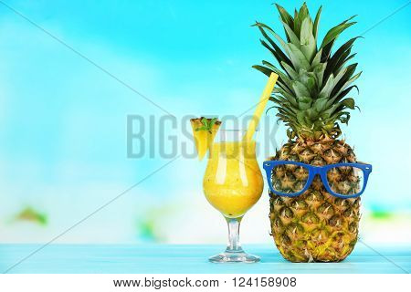 Ripe pineapple with glasses and smoothie in glass on blue blurred background