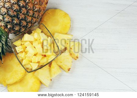 Sliced fresh pineapple in glass saucer on wooden table, top view