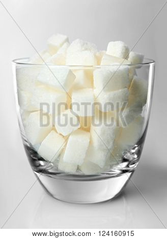 Rocks glass filled with lump sugar on grey background