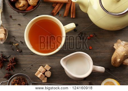 Cup of brewed tea with milk, and brown sugar on wooden table