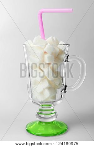 Irish coffee glass with lump sugar and cocktail straw on grey background