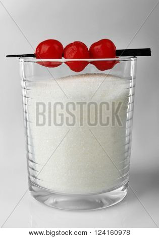 Old fashioned glass with granulated sugar and cocktail cherries on grey background