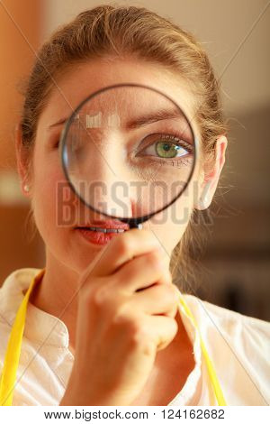 Mature woman female looking through magnifying glass. Investigation or exploration concept.