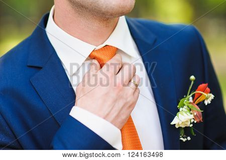 Groom in white shirt and blue suit correcting a orange tie. Ring on his finger. beautiful boutonniere on suit of groom. Man in blue suit shirt and orange tie.