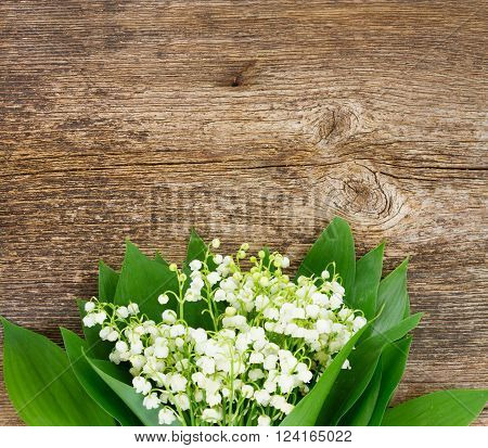 Lilly of valley  fresh flowers and leaves close up on wooden table with copy space
