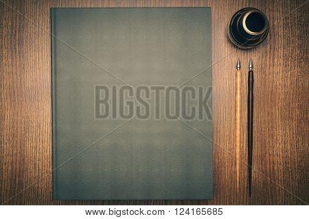 Closed green book, ink-pot and two pens on wooden desktop. Mock up, 3D Render