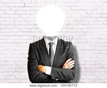 Idea concept with lamp headed businessman on white brick wall background