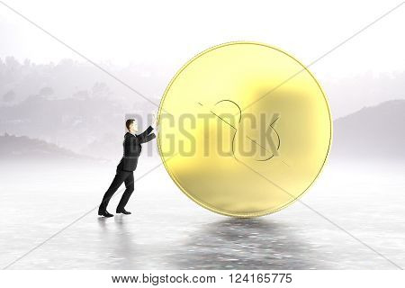 Businessman pushing huge dollar coin on abstract grey background