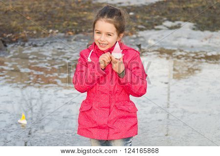 Happy cute little girl in rain boots playing with handmade ships in the spring creek standing in water. Kids play outdoors