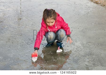 Happy cute little girl in rain boots playing with handmade ships in the spring water puddle. Kids play outdoors