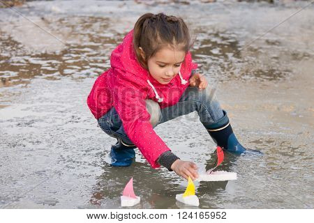 Happy cute little girl in rain boots playing with ships in the spring water puddle. Kids play outdoors