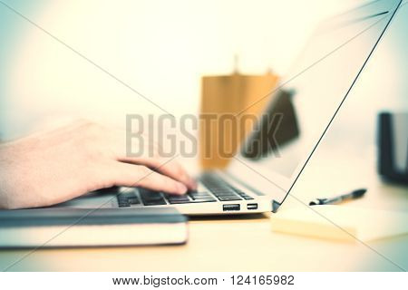 Sideview of a man's hand typing on notebook keyboard