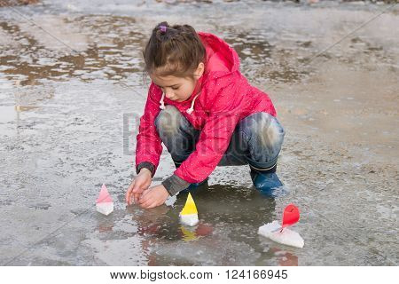 Cute little girl in rain boots playing with colorful ships in the spring water puddle. Kids play outdoors