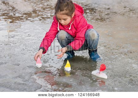 Cute little girl in rain boots playing with handmade colorful ships in the spring water puddle. Kids play outdoors