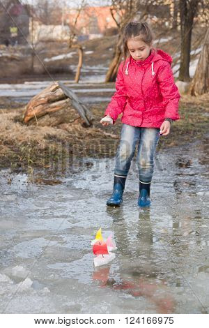 Cute little girl in rain boots playing with handmade colorful ships in the spring creek standing in water. Kids play outdoors
