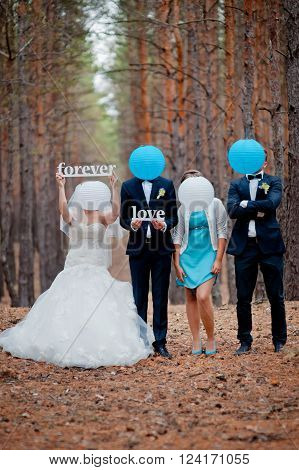 groom, bride and witnesses walking in autumn pine forest.