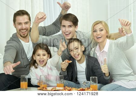 Portrait of a happy family at home with pizza