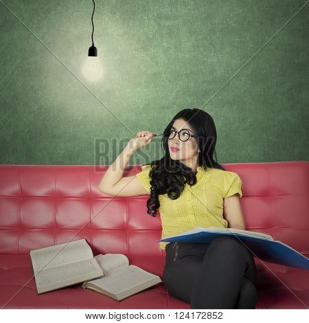 Picture of a smart female student reading book while sitting on the sofa and looking at a bright light bulb