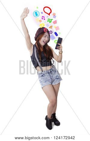 Portrait of teenage girl using social media on her smartphone while standing in the studio