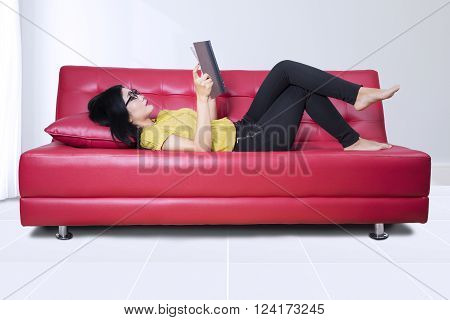 Young Asian woman reading a novel while relaxing and lying on the sofa at home