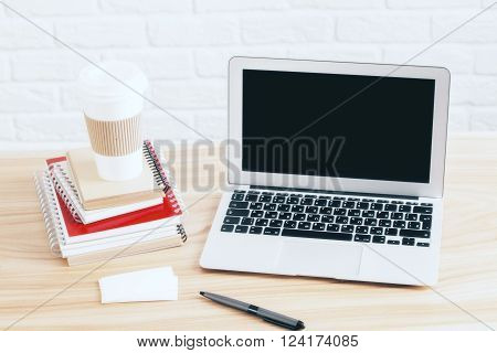 Topview of wooden table with blank laptop screen and coffee cup placed on stack of copybooks. Mock up