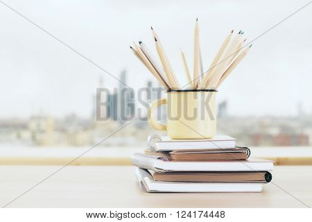 Yellow mug with wooden pencils on stack of copybooks and blurry city in the background