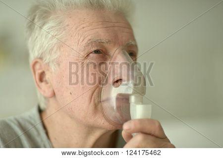 Portrait of elderly man with flu inhalation