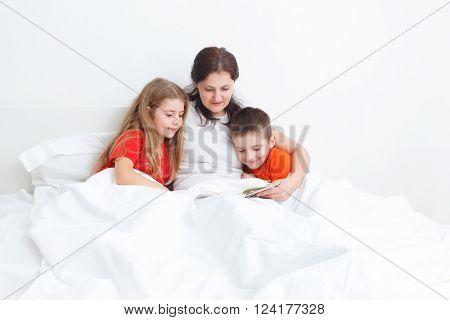 mom reading a book in bed for her childs before sleep