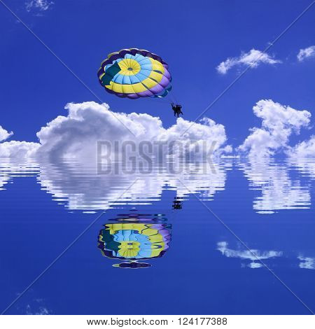 Parachute tandem on the blue sky with white clouds during the summer flying over the clear lake. Reflection in the silent lake.