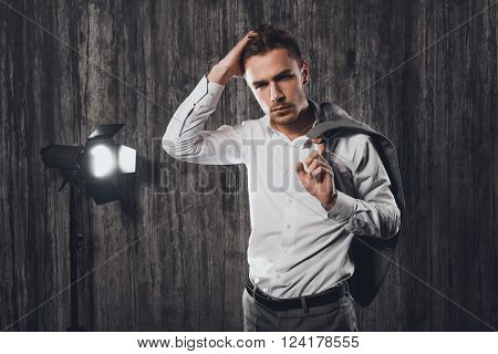 Portrait Of Handsome Businessman Touching His Hair And Holding Jacket