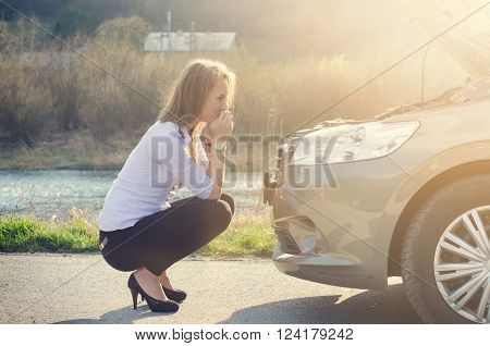 Woman crouching on the road next to a car. Sad person. Damaged car. Natural background. Car accident.