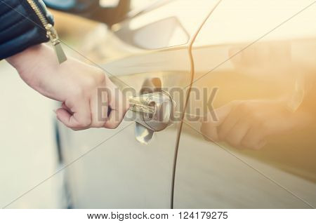Woman with car key. Opening car door. Woman´s hand unlocking a door on a car. Sunlight. Transportation.