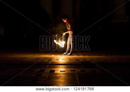 Sofia Bulgaria - March 19 2016: An art performer in the dark is preparing herself before acting during a fire show.