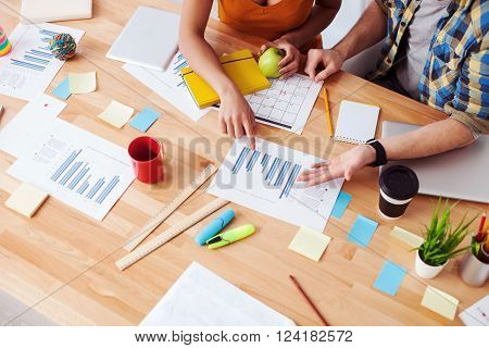 Close up of arms of two office workers discussing new project. They are sitting at the desk. The woman is pointing finger at document