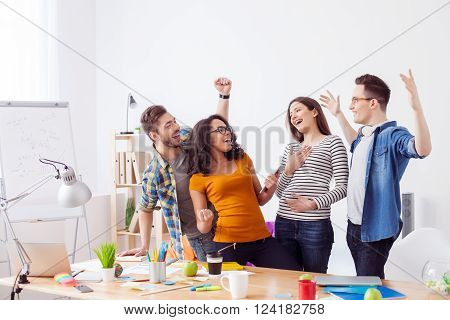Everything is great.  Cheerful creative team has done their project successfully. They are standing in office and laughing. The men are raising arms up with joy